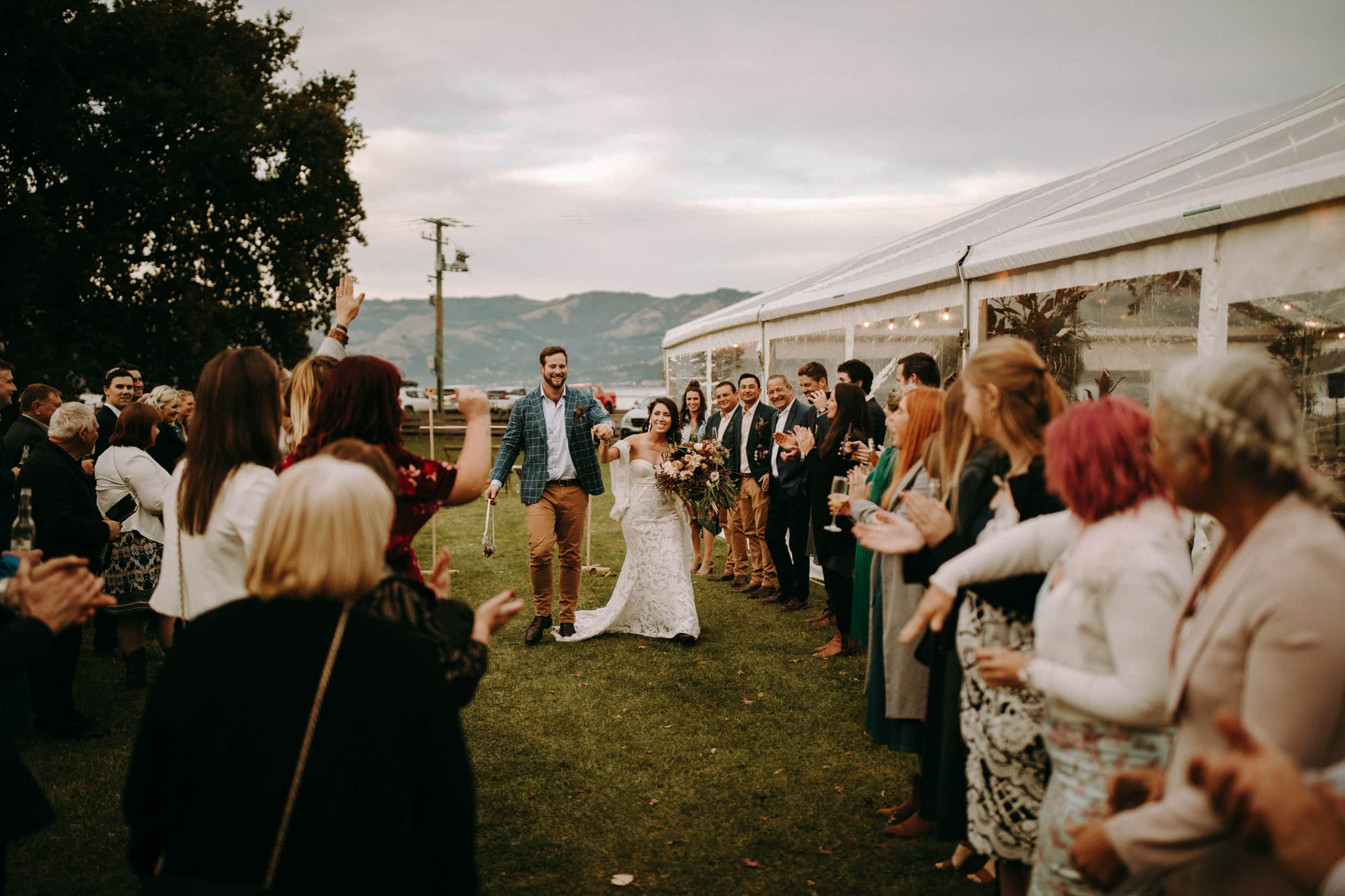 A newly wedded couple is walking towards their wedding guests next to a tent.