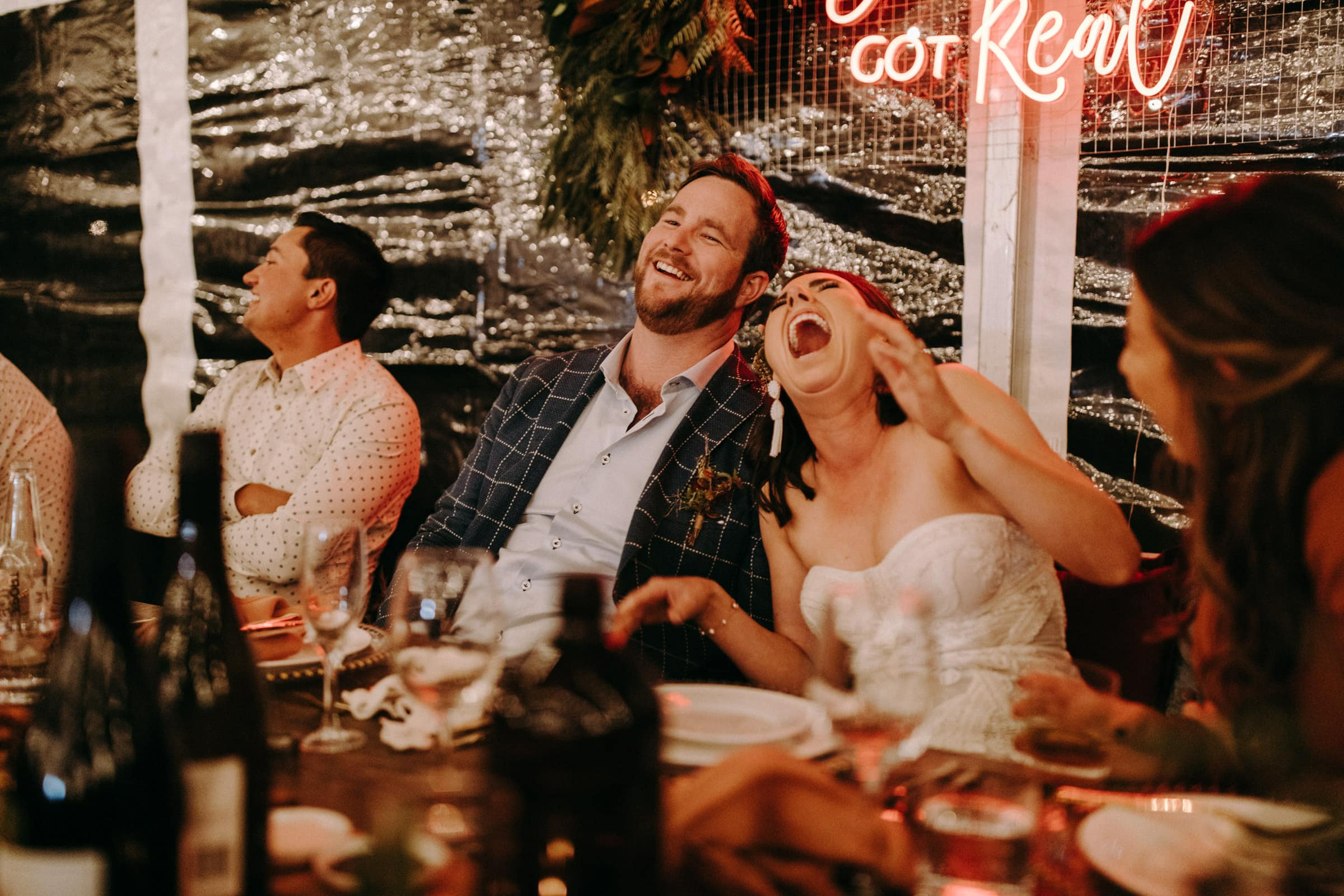 A wedding couple is sitting at the wedding table and is laughing.
