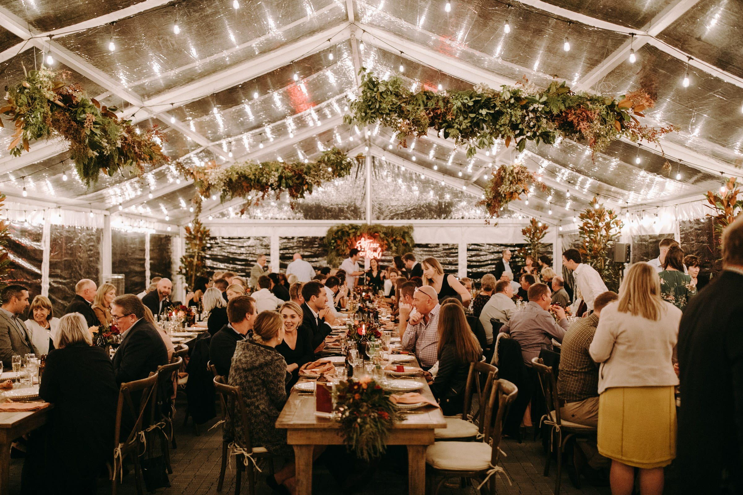 A big tent is decorated with light bulbs and branches and guests are sitting at three rows of tables.