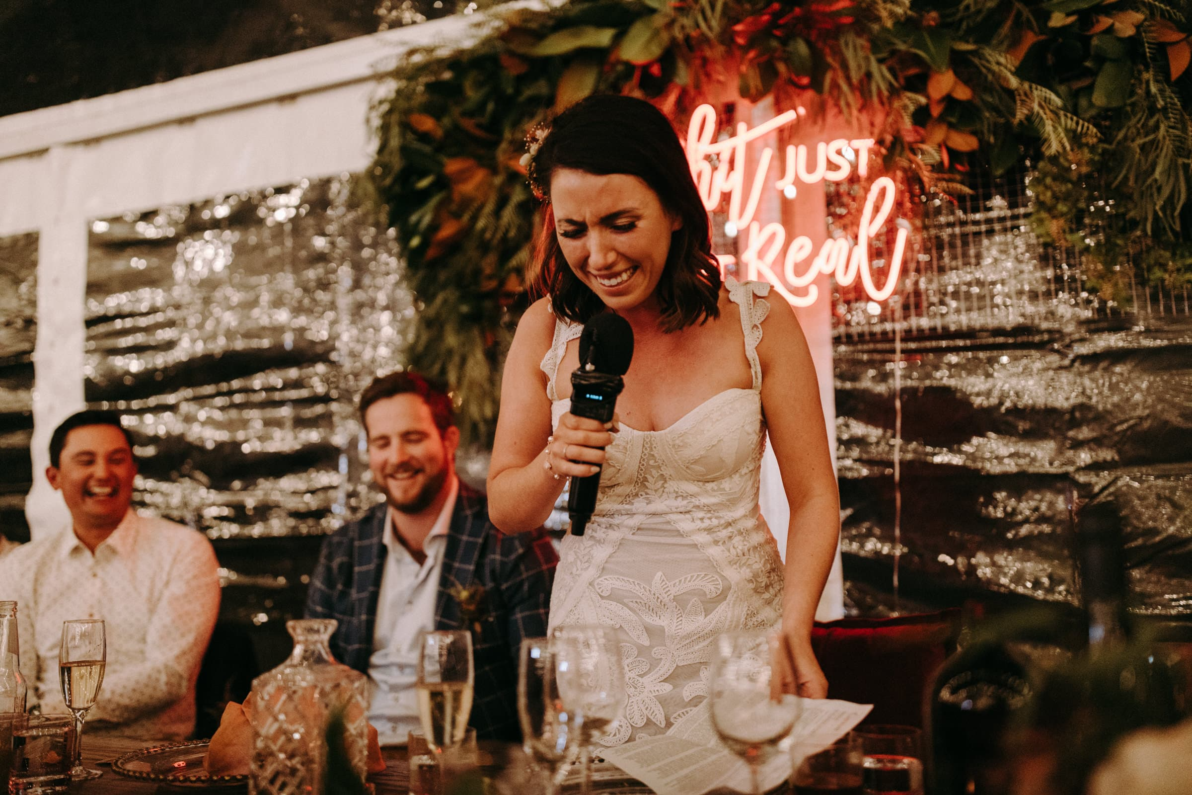 A bride is standing and talking into a microphone and her groom is sitting at the wedding table.