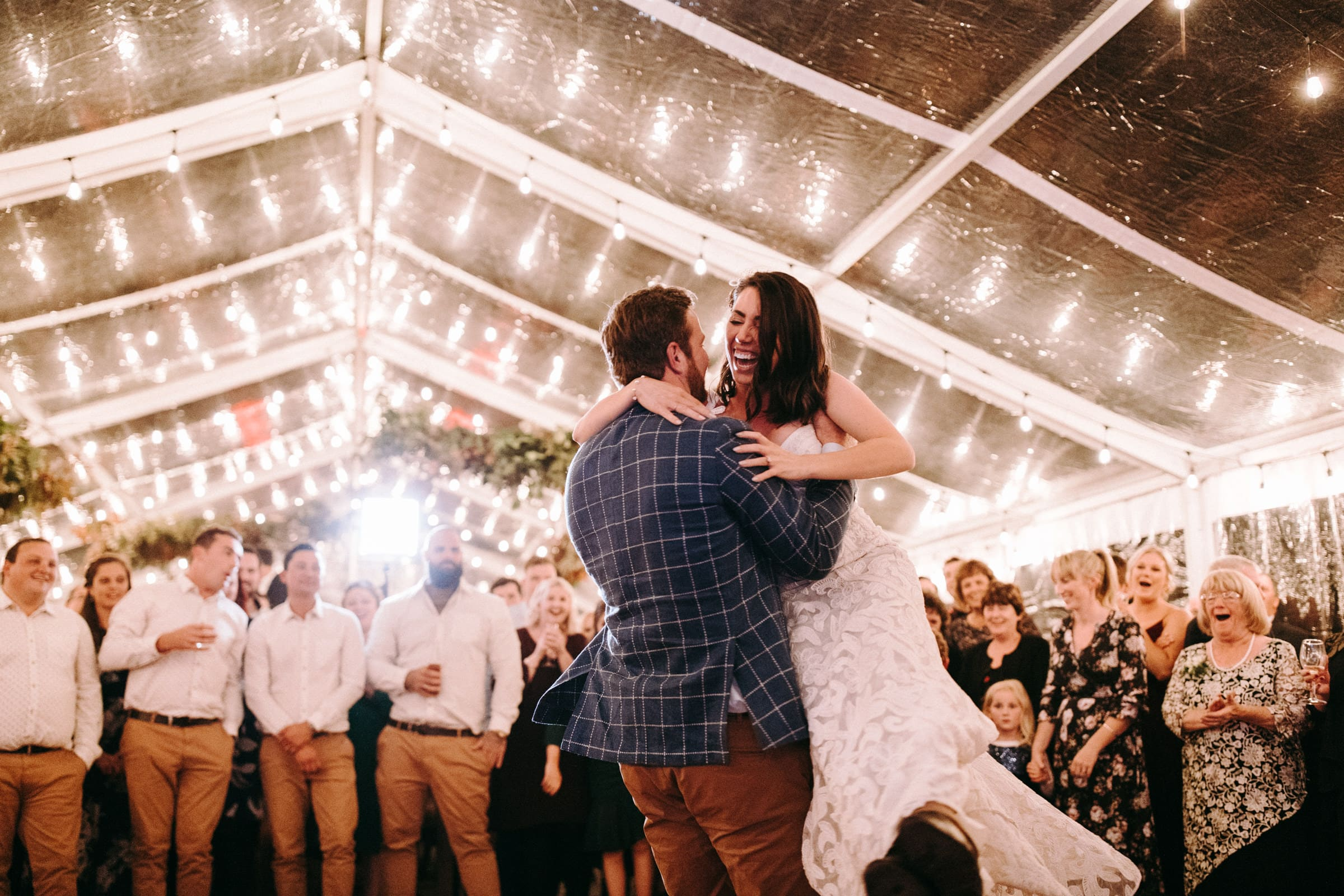 A wedding couple is dancing in a tent with their wedding guests next to them.