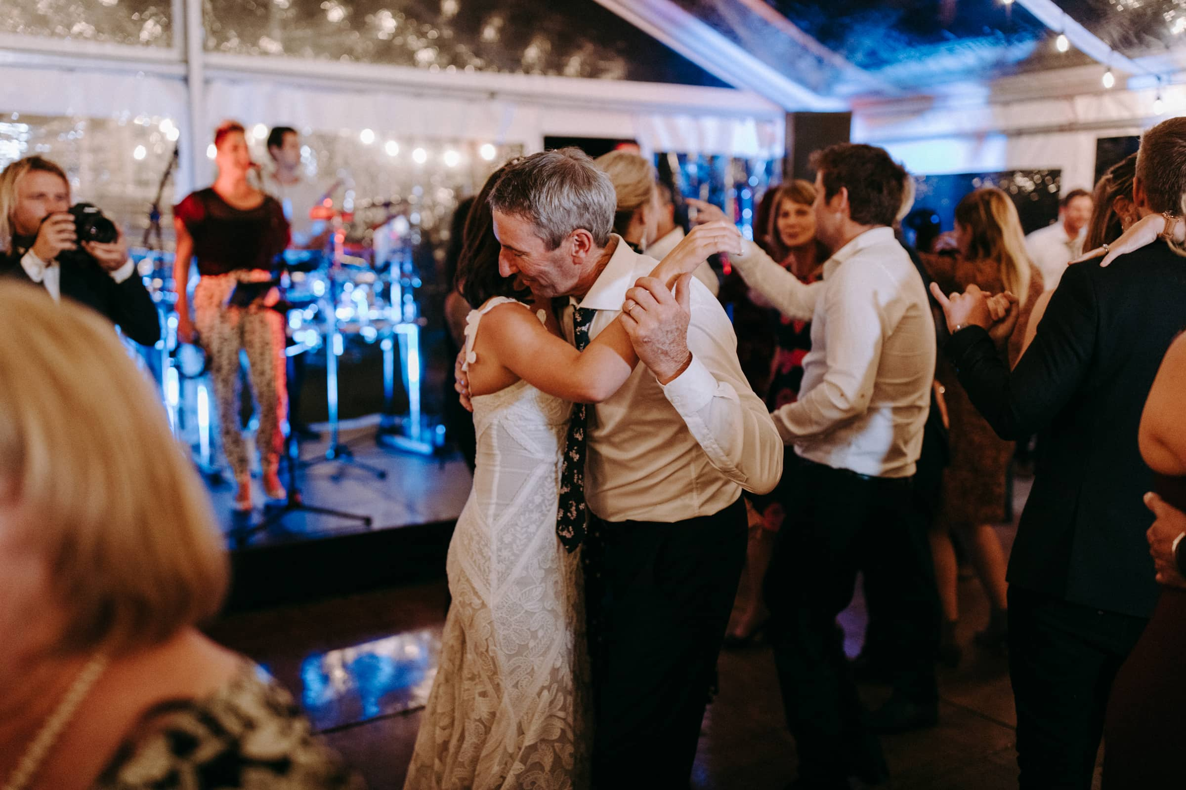 A bride and her father are dancing next to other wedding guests.