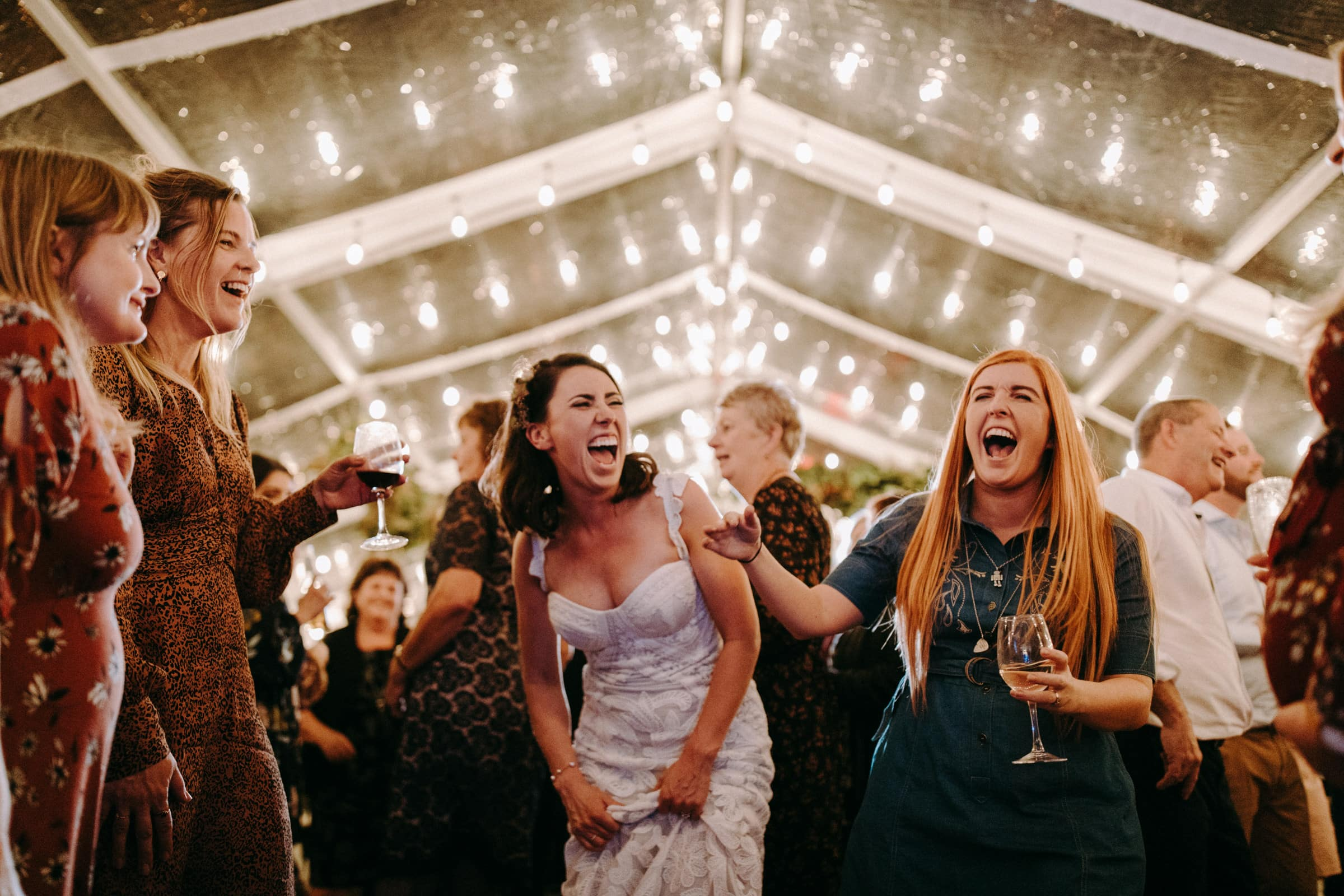 A bride and her wedding guests are laughing and dancing in a tent.