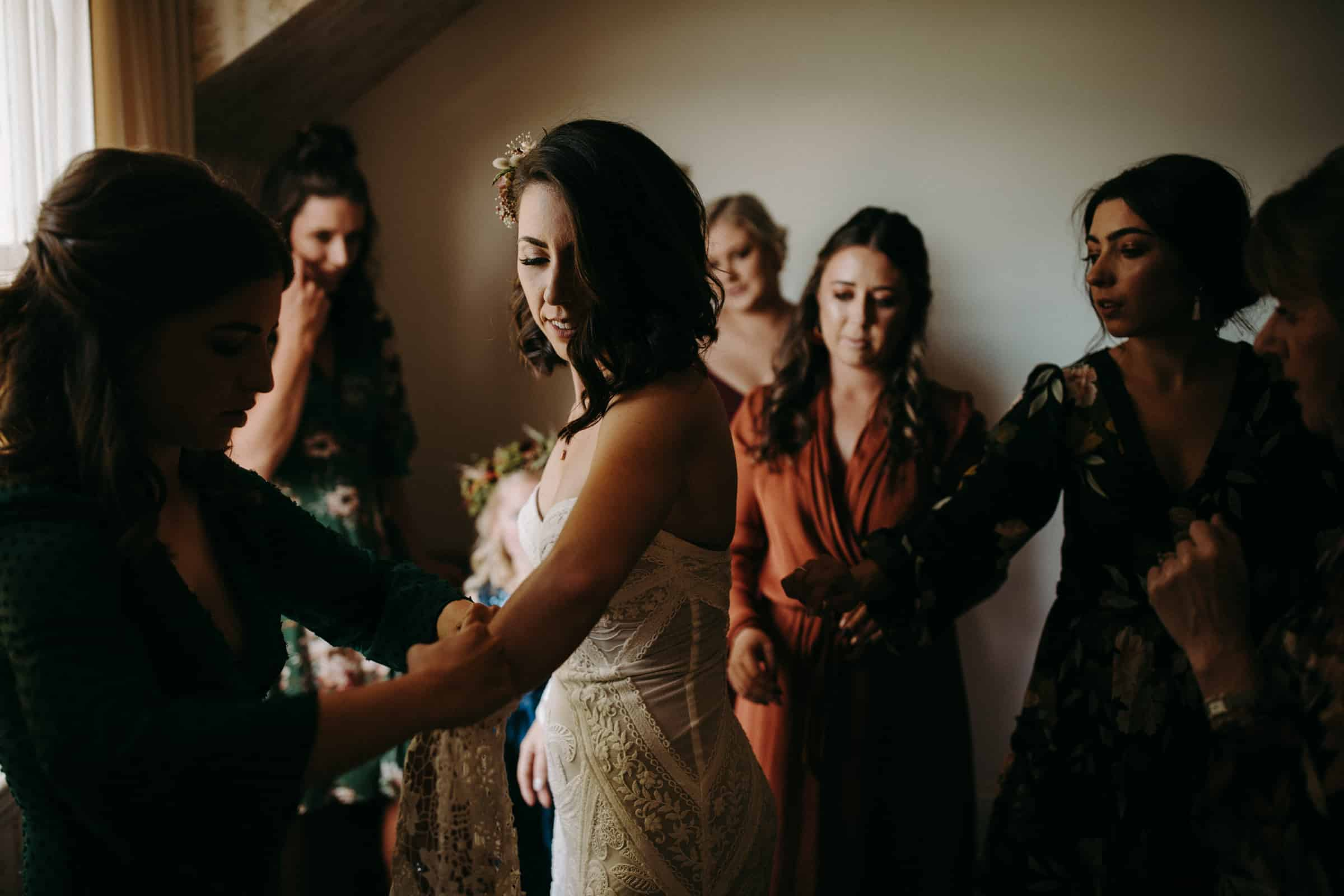 A bride is getting dressed and her bridesmaids are standing next to her.
