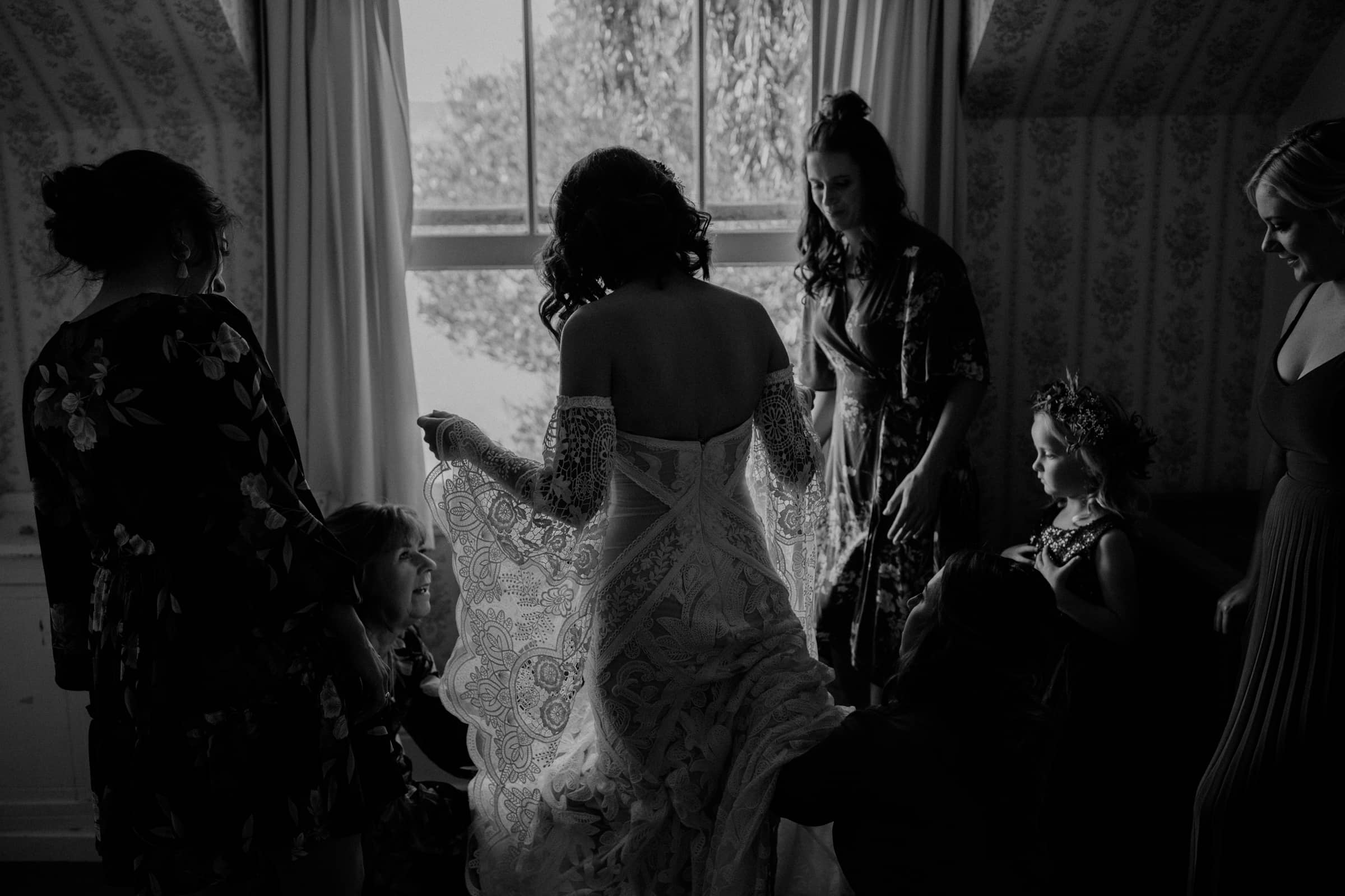 A bride is wearing her wedding dress and is standing in front of a window with her wedding guests.