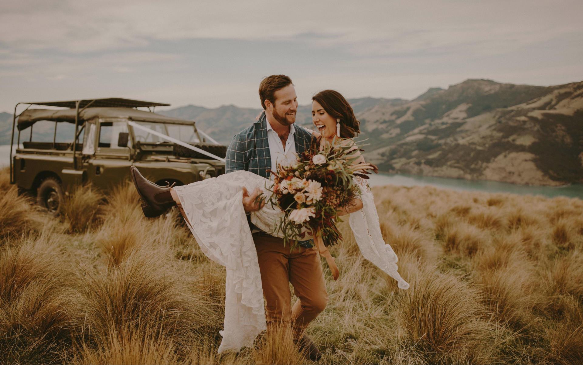 Ein Bräutigam trägt seine Braut auf Händen durch eine Wiese.