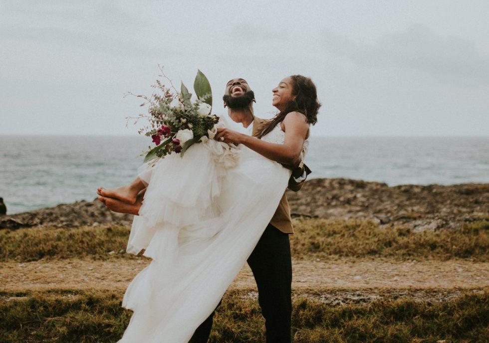 Ein Bräutigam hält seine Braut in den Armen und die beiden befinden sich in Barbados.