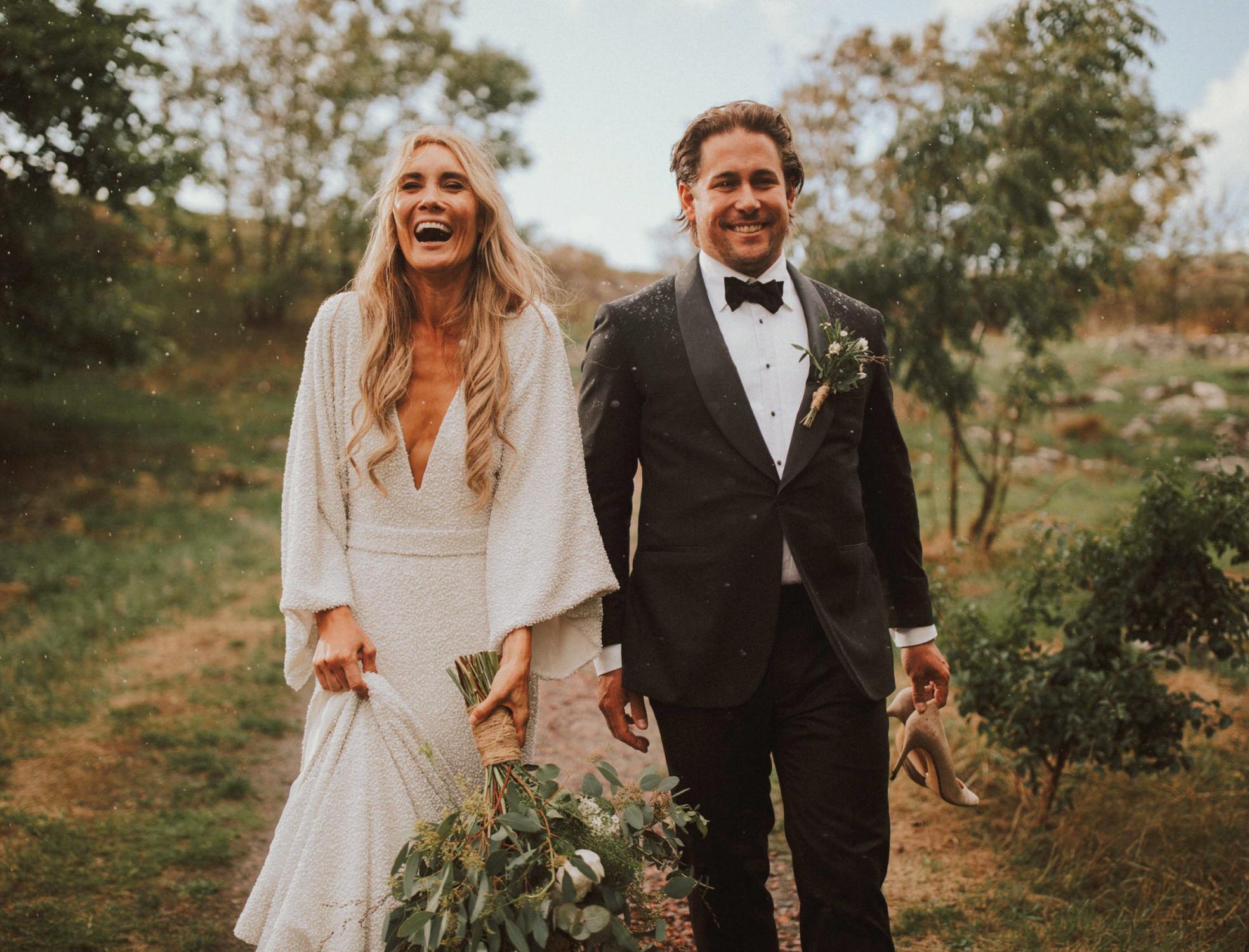 Ein Hochzeitspaar läuft einen Feldweg entlang.