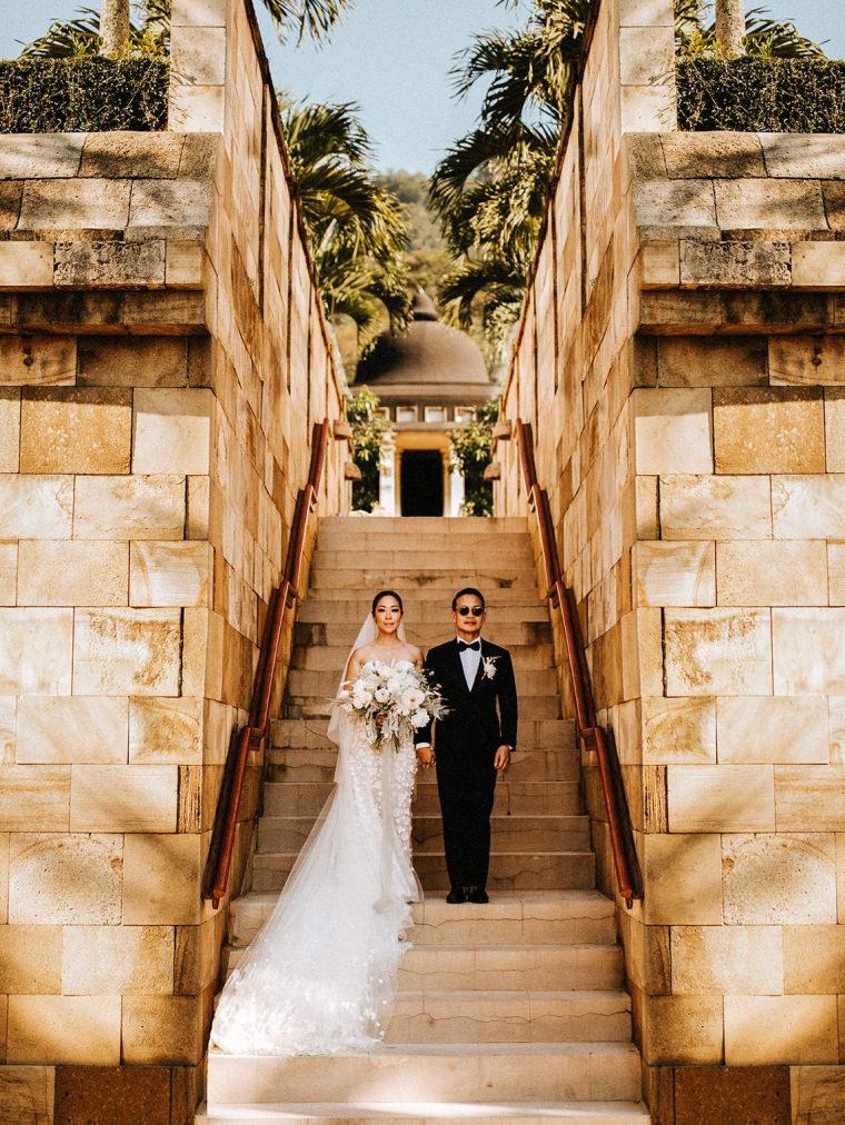 Ein Hochzeitspaar steht auf einem Treppenaufgang.