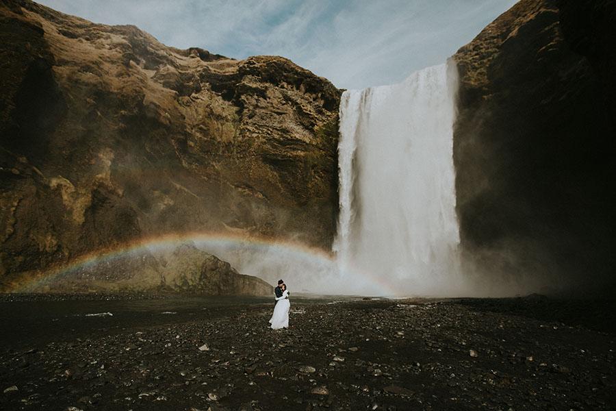 Ein Hochzeitspaar steht vor einem Wasserfall.