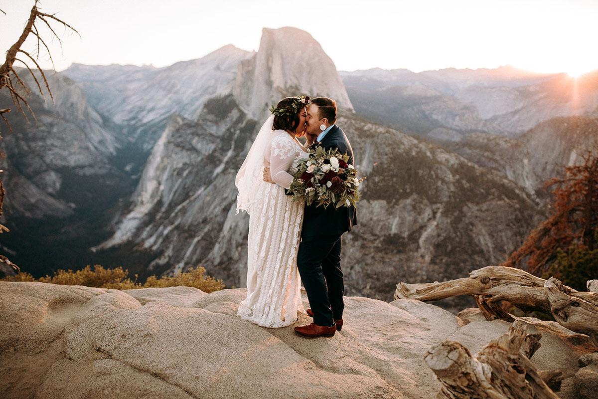 Ein Hochzeitspaar küsst sich und steht auf einem Berg.