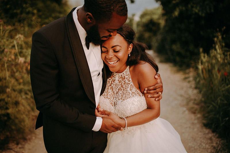Ein Hochzeitspaar liegt sich in den Armen und lächelt.