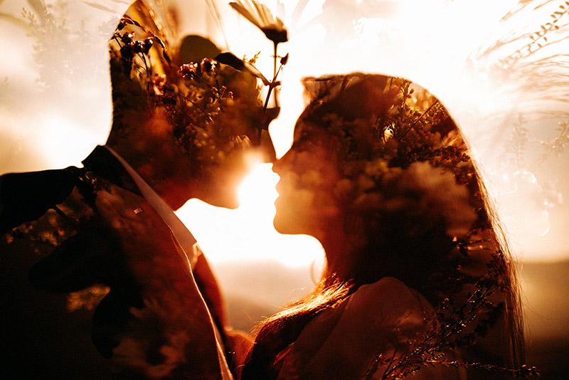 Ein Paar ist kurz davor sich zu küssen und im Hintergrund geht die Sonne unter.