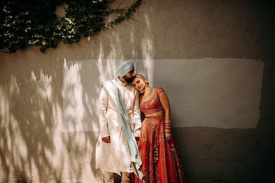 Ein Hochzeitspaar hält sich aneinander fest und steht vor einer Mauer.