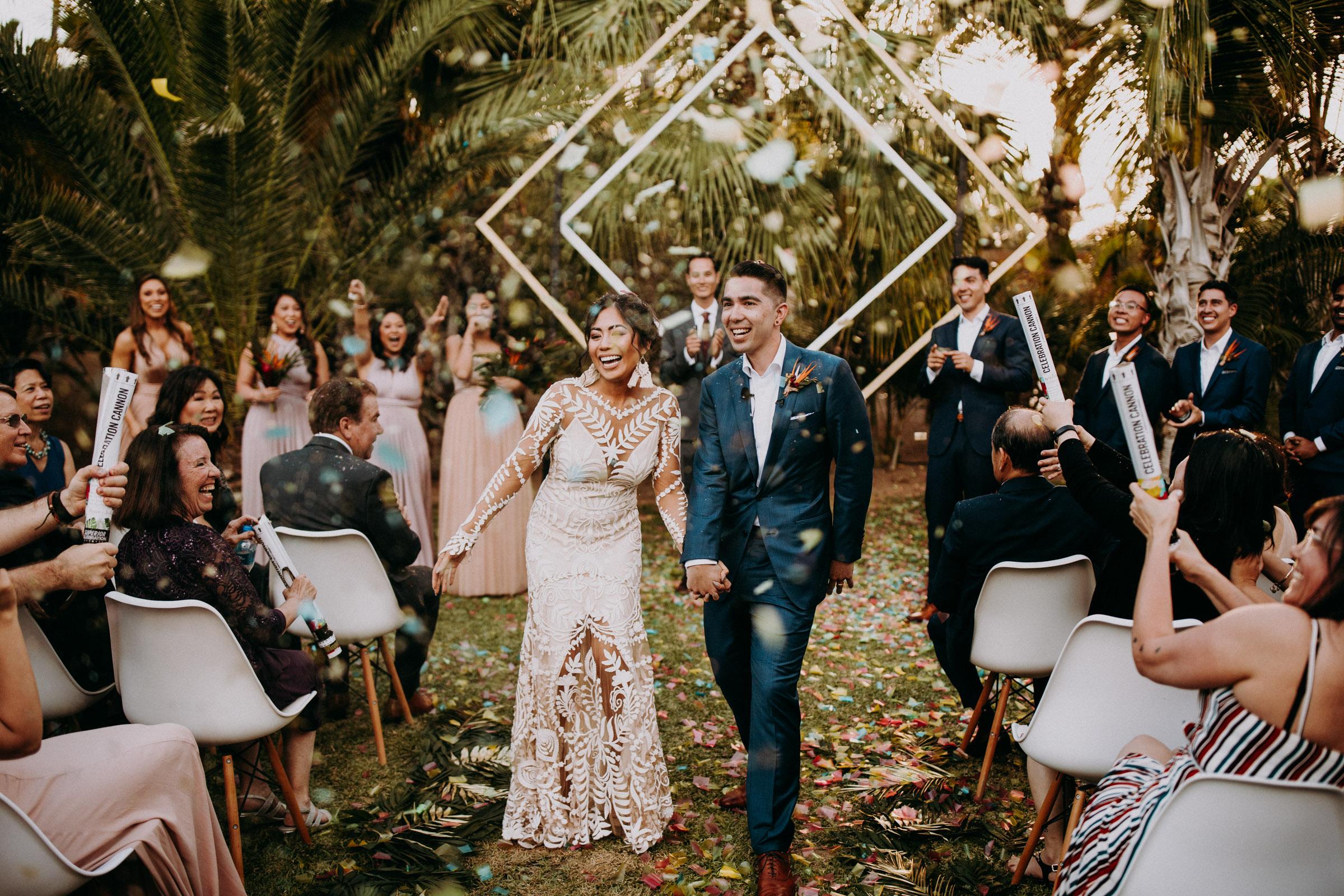 Ein Hochzeitspaar läuft an denGästen vorbei, die Konfetti auf die beiden werfen.